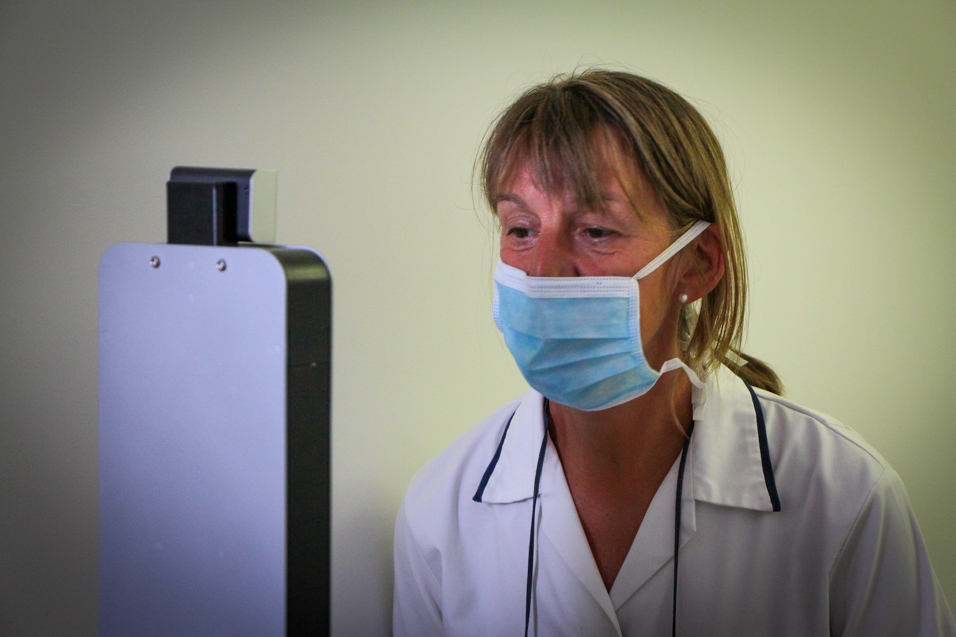 body temperature scan at a care home, wearing a mask, mask detection, temperature testing machine